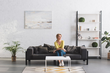 beautiful woman sitting on couch and looking away at home Wall mural