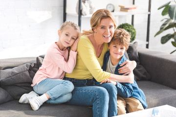 happy mother and adorable little kids sitting on sofa and smiling at camera