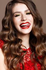 A young girl in a brilliant red dress and evening makeup. Beautiful smiling model in a New Year's image with curls. Shining skin, festive mood. Beauty face. The photo was taken in the studio.