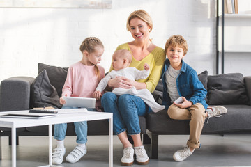 happy mother smiling at camera while sitting on couch with three adorable children