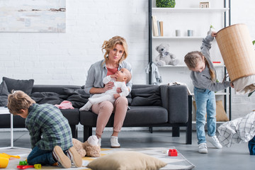 exhausted mother with infant child sitting on couch and looking at camera while naughty siblings playing at home Wall mural