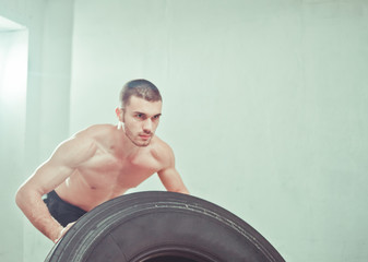 Concept functional training workout gym. Fitness man flipping tire wheel at gym