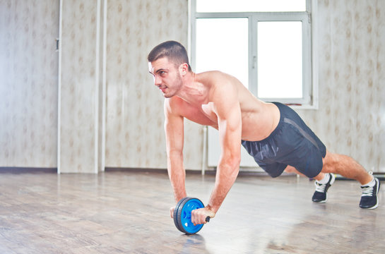 Handsome sportsman workout with abdominal ab roller at hall with window