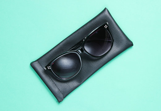 Sunglasses with protective leather case on blue background.