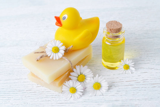 baby care products, soap bar, massage oil and fresh chamomile flowers