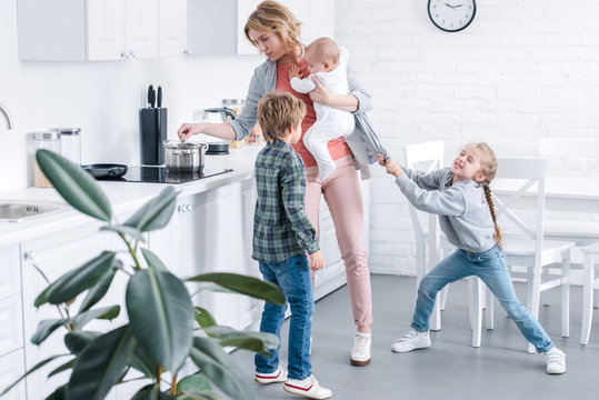 tired mother holding infant child and cooking while naughty children playing in kitchen