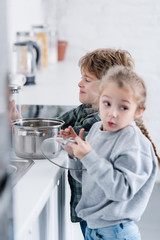 adorable brother and sister washing pan in kitchen
