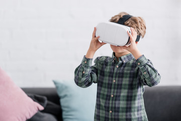 adorable little boy using virtual reality headset at home