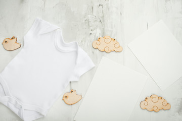 Layout Flat Lay a white children's body shirt, on a white background, with white postcards and children's wooden toys. Choose design and placement of logos, advertising