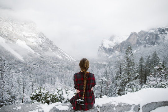 woman with camera sitting looking at tunnel view in yosemite in winter