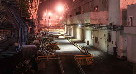 Port warehouse with ramp and cranes at night. Stacked PVC and steel pipe ready for shipment