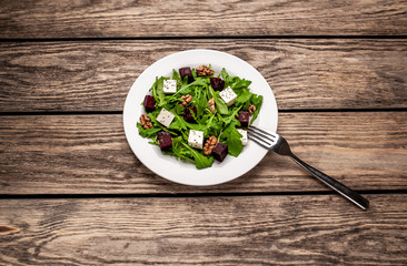Fototapeta Salad of arugula, cheese, beet, walnut, on a wooden table