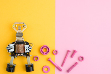 Metal robot, screws and washers, spring, colored with multicolored paint. Colorful background. Pink and yellow. Concept, background, flat lay.  Free space for text.
