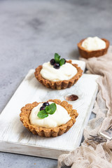 Mini tarts (tartlets) with whipped cream or custard and fresh berries served with mint. Homemade dessert. Grey background. Copy space.