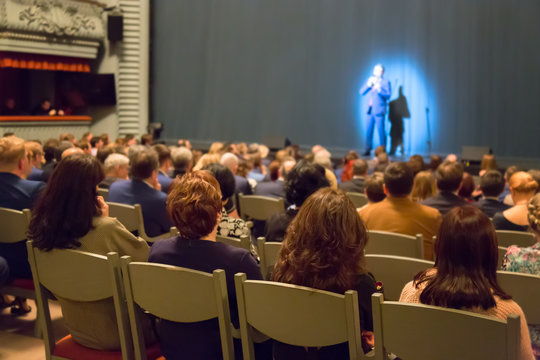 Man appears on stage in theater with many people