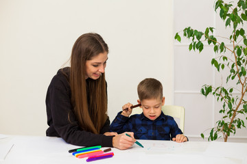 woman teaches a young boy paint markers