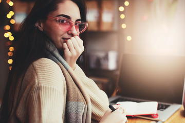 Pretty brunette woman do her work at cafe, wear glasses and chat in laptop near the window. - Image