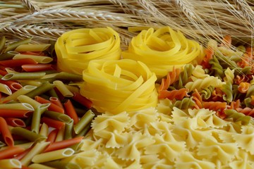 Different types of pasta and wheat ears close-up.