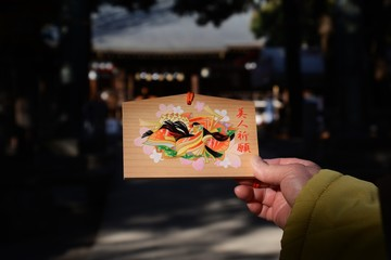 "In Japan called ""Ema"" /  A votive picture tablet which we offer to a shrine or temple when we pray for something of after our prayers are answered."