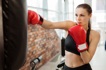 beautiful young girl in red boxing gloves is engaged in training in the gym