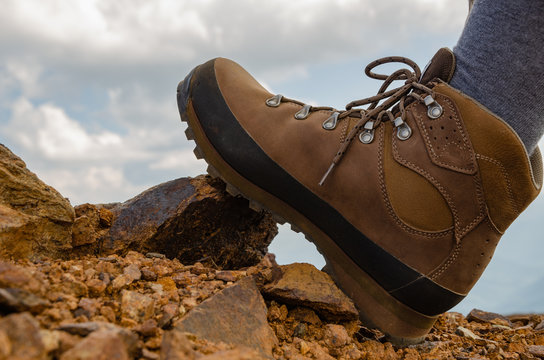 Foot in hiking shoe on a stone and a surface of orange soil