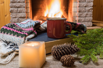 Cozy scene before fireplace with red enameled mug with tea, and wool scarf.