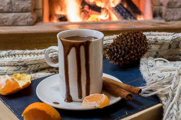 Cozy scene before fireplace with mug of hot chocolate, cones, tangarine and wool scarf.