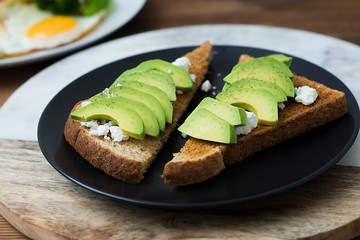 Breakfast sandwich on toast bread made with fresh sliced avocado, cream cheese and seeds, from above