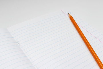 Yellow pencil on the background of a white lined sheet of notebook close-up with copy space