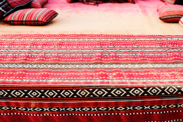 Decorative pattern in the style of arabesque on a carpet in the desert with pillows