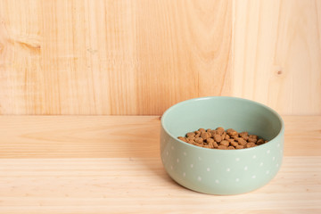 Dry cat food in a green porcelain bowl on a wooden background