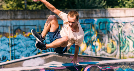 Sporty man jumping over obstacles in skatepark
