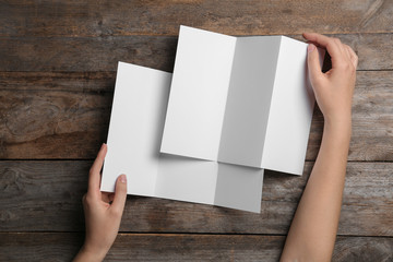 Woman with blank brochures on wooden background, above view. Mock up for design