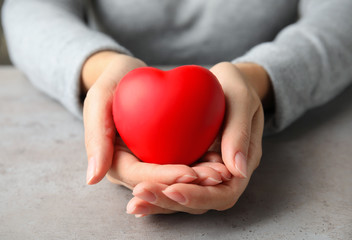 Woman holding red heart on gray table, closeup. Cardiology concept