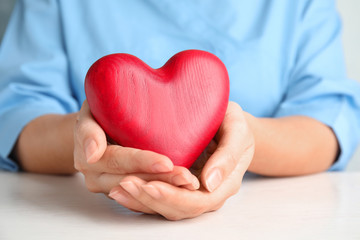 Doctor holding red heart at wooden table, closeup. Cardiology concept