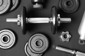 Flat lay composition with dumbbell and parts on dark background