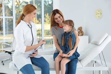 Mother and daughter visiting pediatrician. Doctor working with patient in hospital