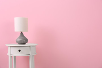 Stylish lamp on table against color background. Space for text