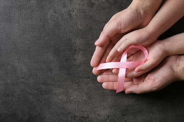 Woman and girl holding pink ribbon on grey background, top view with space for text. Breast cancer awareness