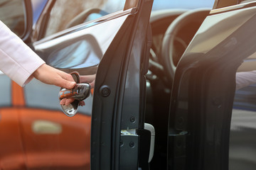 Closeup view of woman opening car door