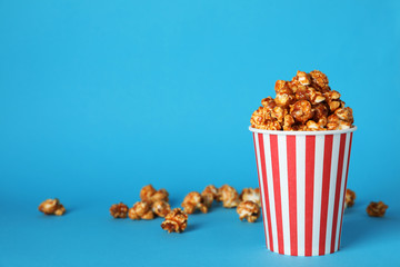 Caramel popcorn in paper cup on color background. Space for text