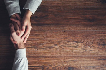 couple hand on wooden table