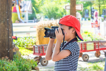 Hand boy holding the camera Taking pictures in park.