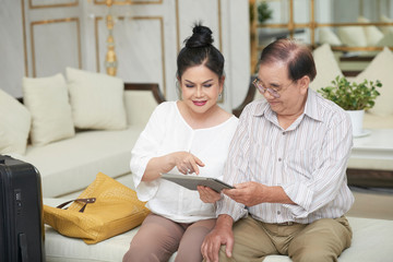 Smiling aged Vietnamese travelers reading information on tablet computer
