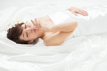 白いドレスを着た髪飾りつけた横になる女性(アップ)