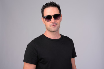 Portrait of happy handsome man smiling with sunglasses against white background