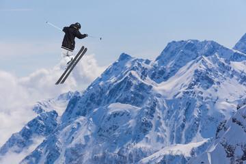 Flying skier on snowy mountains. Extreme winter sport, alpine ski. Copy space.