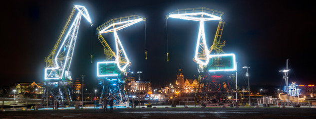 Illuminated old port cranes on a boulevard in Szczecin City at night Wall mural