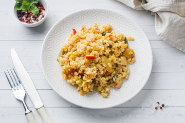 Pilaf with vegetables and chicken in a gray plate on a light background.
