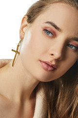 Closeup portrait of a pretty girl with natural makeup and light brown hair, wearing a long golden earring in the shape of a cross. The woman with gray eyes is looking to the side on white background.